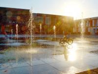 Das Rathaus mit der Fontänenanlage davor und zwischen den Fontänen fährt ein Kind mit dem Fahrrad