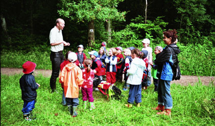 """Der Förster erklärt einer Gruppe von Kindern Interessantes zum Thema """"Wald"""""""