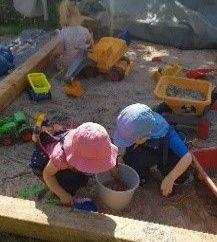 Kinder spielen im Sandkasten im Garten