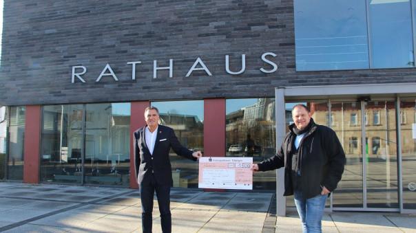 Bürgermeister Thomas Hölsch und Sven Laichinger halten zusammen den Spendenscheck