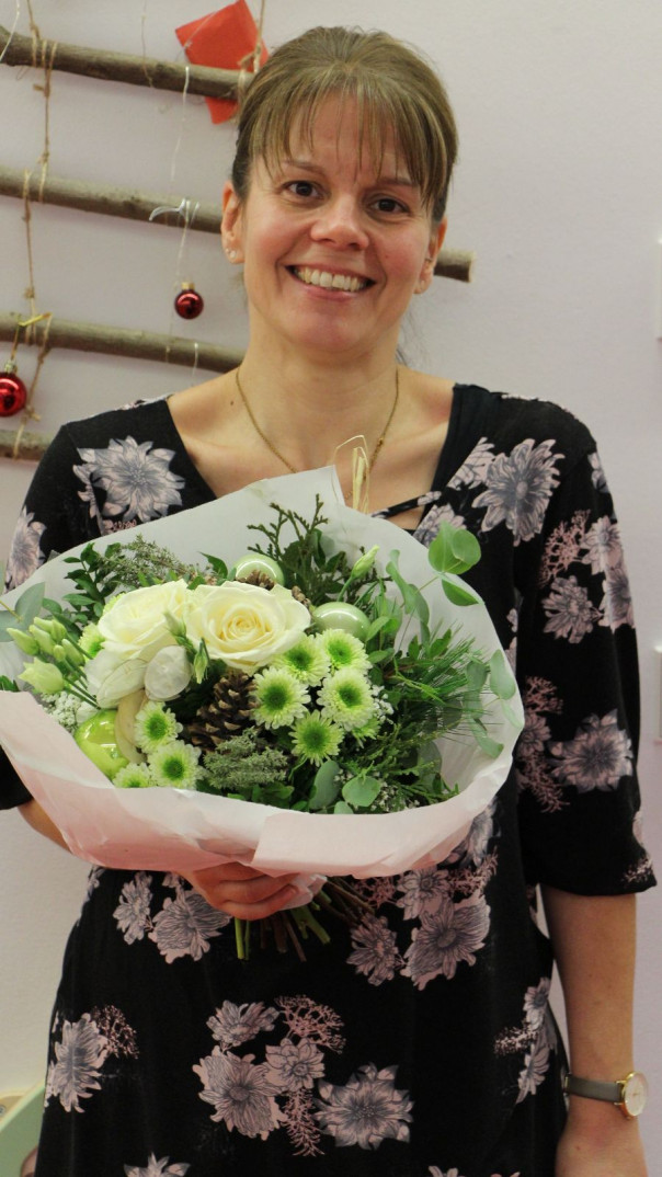 Frau Gualano mit dem ihr übergebenen Blumenstrauß