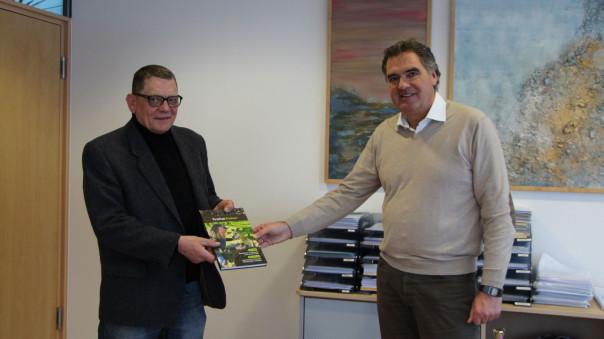 Karl-Heinz Klink übergibt Bürgermeister Thomas Hölsch das Trüffel-Buch